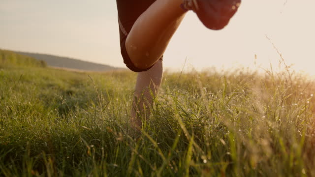 slo mo legs of a female runner running in grass - cross country running stock videos & royalty-free footage