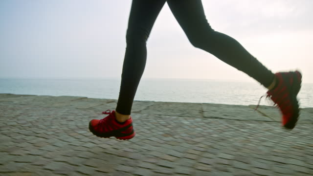 slo mo ts legs of a female runner running on a pathway along the sea in the early morning - cardiovascular exercise stock videos & royalty-free footage
