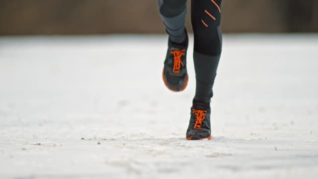 SLO MO Legs of a female runner running on snow covered trail