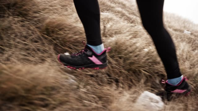 slo mo ts legs of a female runner running up a mountain on a grassy slope - cross country running stock videos & royalty-free footage