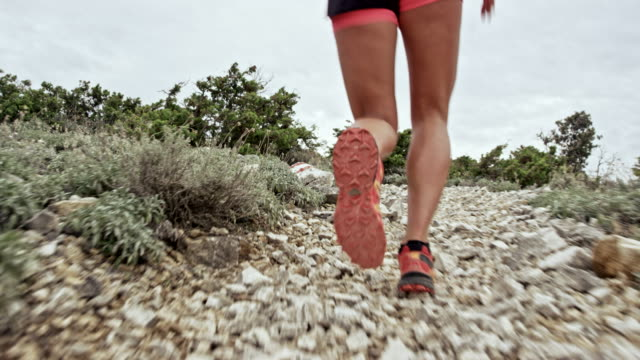 Legs of a female runner running up the mountain on a rocky trail