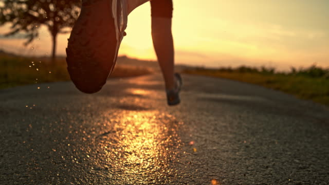 slo mo legs of a female runner splashing on wet road - tarmac stock videos & royalty-free footage