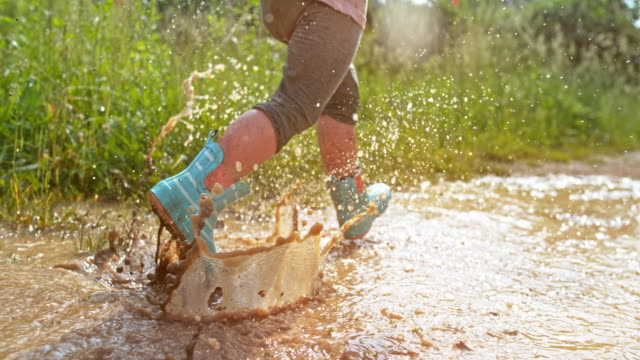 slo mo legs of a little child wearing rainboots running across the muddy puddle - mud stock videos & royalty-free footage