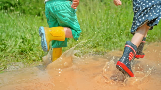 slo mo legs of a little girl and a boy running across a muddy puddle in sunshine wearing their rain boots - wellington boot stock videos & royalty-free footage