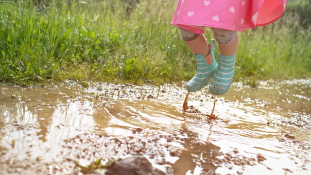 slo mo legs of a little girl jumping in a muddy puddle wearing cute rain boots - puddle stock videos & royalty-free footage