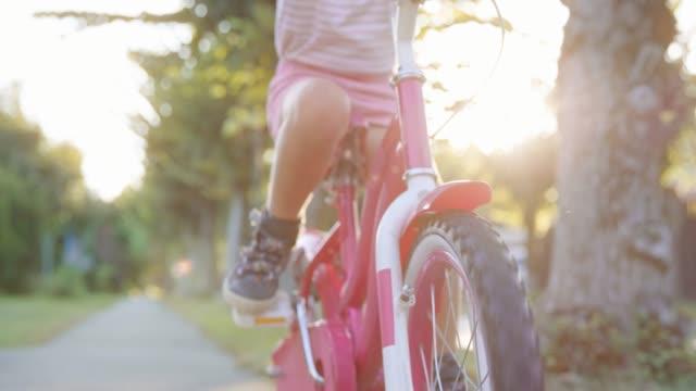 vidéos et rushes de slo mo jambes d'une petite fille, poussant les pédales de son vélo dans le quartier de banlieue au soleil - petites filles