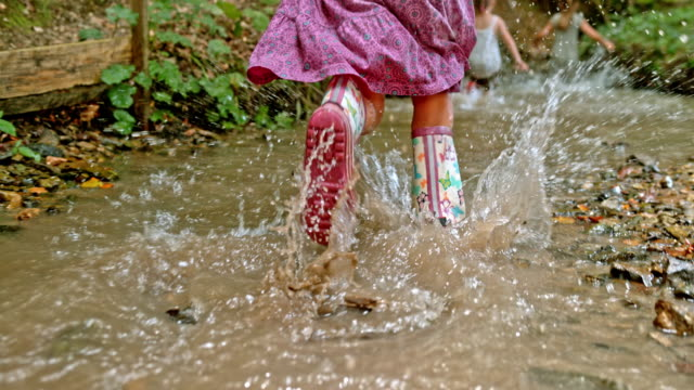 slo mo legs of a little girl wearing a pink dress and rain boots and running across a small creek in the forest - dress stock videos & royalty-free footage