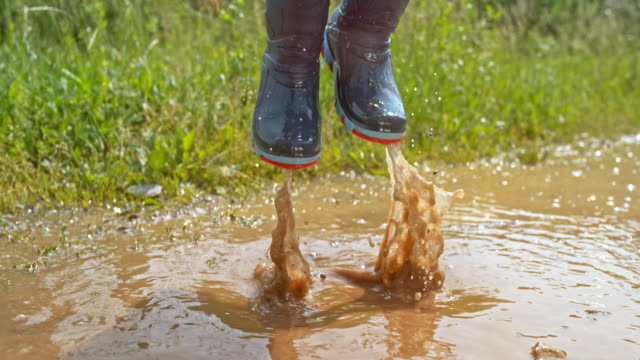 slo mo legs of a little kid wearing rain boots jumping high in a muddy puddle - children only stock videos & royalty-free footage