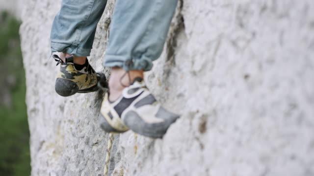 legs of a male climber ascending the cliff - arrampicata su roccia video stock e b–roll