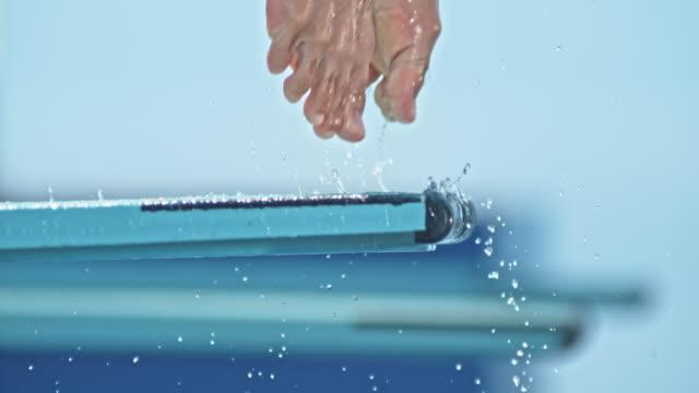 vídeos de stock e filmes b-roll de slo mo legs of a male high diver jumping off the diving board - mergulho desporto