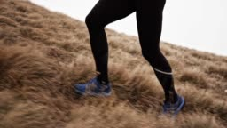 SLO MO TS Legs of a male runner ascending a mountain on a grassy slope