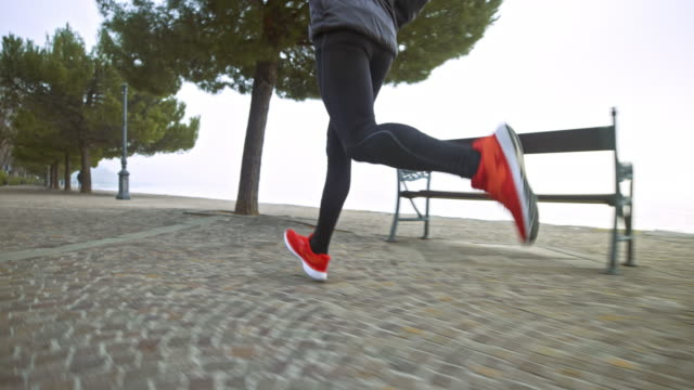 slo mo ts legs of a male runner running on a wide footpath along the foggy sea - leggings stock videos & royalty-free footage
