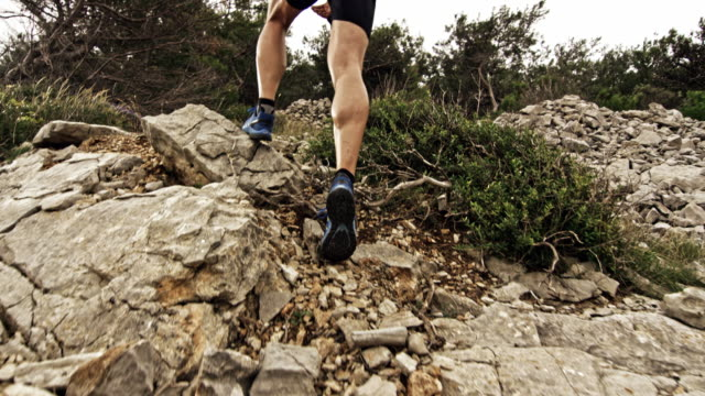 slo mo legs of a male runner running up the mountain on a rocky trail - uphill stock videos & royalty-free footage