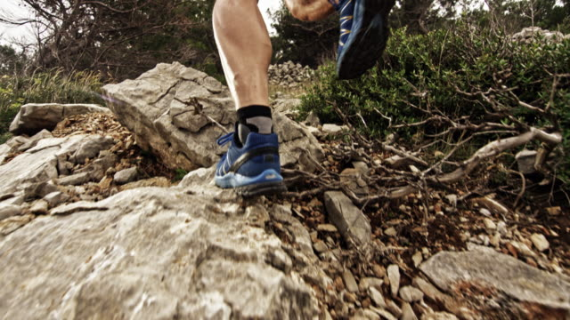 slo mo legs of a male runner running up the rocky mountain - uphill stock videos & royalty-free footage