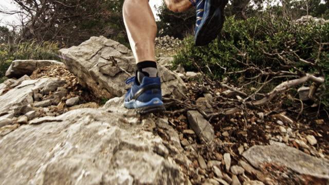 vídeos de stock, filmes e b-roll de slo mo as pernas de um corredor subindo a montanha rochosa - colina acima