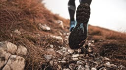 SLO MO Legs of a male runner running uphill and kicking gravel into the air