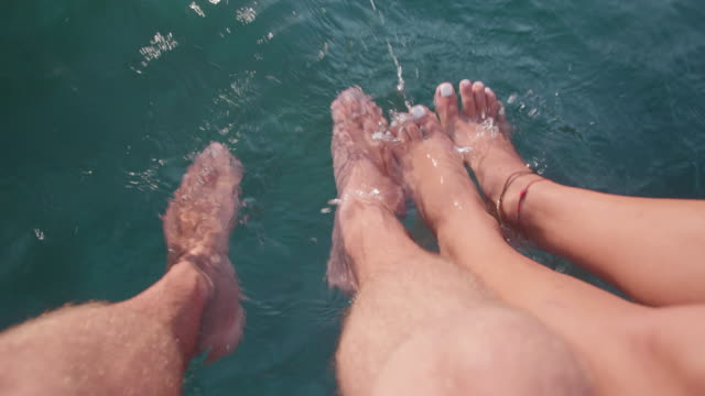 legs of a man and woman couple relaxing and resting at the sea. - zen like stock videos & royalty-free footage