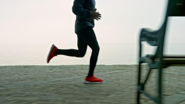 slo mo ts gambe di un uomo che corre su un sentiero lungo il mare in una mattina nebbiosa - limb body part video stock e b–roll