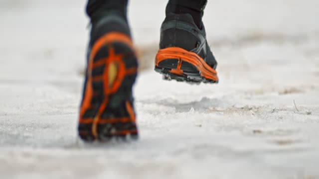 SLO MO Legs of a runner running on snow covered walkway