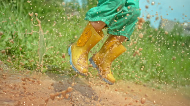 vídeos de stock e filmes b-roll de slo mo legs of a small boy jumping high up in the air in a muddy puddle wearing his rain boots and making a splash - bota