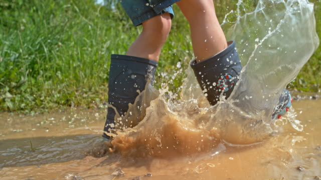 slo mo legs of a small boy kicking the water in the puddle with the rain boot - wellington boot stock videos & royalty-free footage