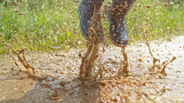 泥の水たまりに着陸中のスプラッシュを作る小さな男の子の slo mo 足 - ヨゴレ点の映像素材/bロール