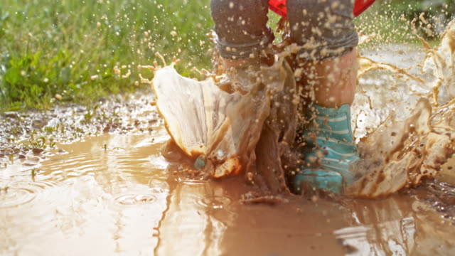 slo mo legs of a small child jumping in a muddy puddle wearing rainboots and a raincoat - mud stock videos & royalty-free footage