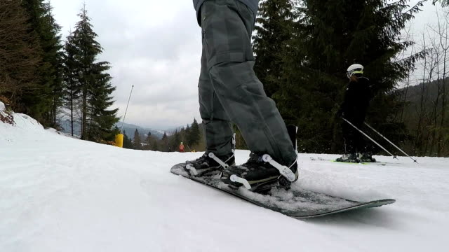 legs of a snowboarder with a snowboard closeup. - ski holiday stock videos & royalty-free footage