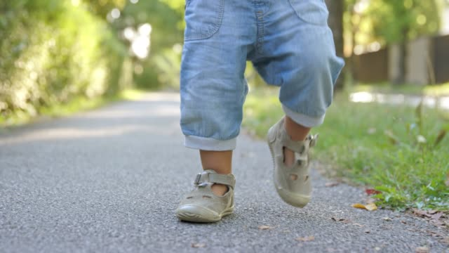 slo mo ds legs of a toddler walking on a sidewalk - jeans stock videos & royalty-free footage