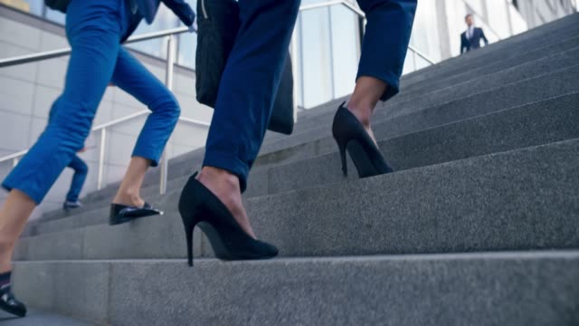 slo mo ts legs of a woman in a business suit and high heels walking up the stairs outside a modern office building - edificio adibito a uffici video stock e b–roll