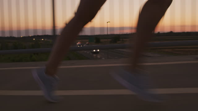 slo mo legs of a woman running across a bridge at dusk - human foot stock videos & royalty-free footage