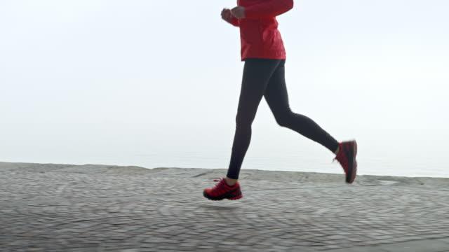slo mo ts gambe di una donna che corre su un sentiero lungo il mare in una mattina nebbiosa - limb body part video stock e b–roll