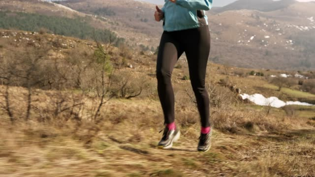 Legs of a woman running up the mountain trail in sunshine