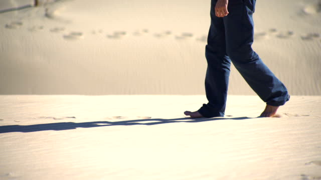 legs of a young man walking in a dune sand in the desert - footprint stock videos and b-roll footage