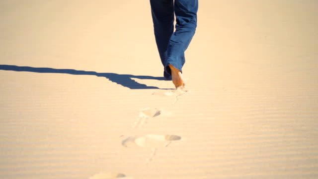 legs of a young man walking in a dune sand in the desert - human limb stock videos & royalty-free footage