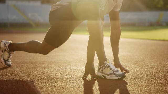 SLO MO jambes d'un homme afro-américain qui s'étend dans le stade sur la piste au soleil couchant