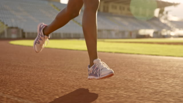 slo mo ts legs of an african-american woman running in stadium at sunset - pista di atletica leggera video stock e b–roll