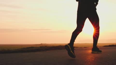 vídeos y material grabado en eventos de stock de ms legs de un irreconocible jogger en carretera - correr