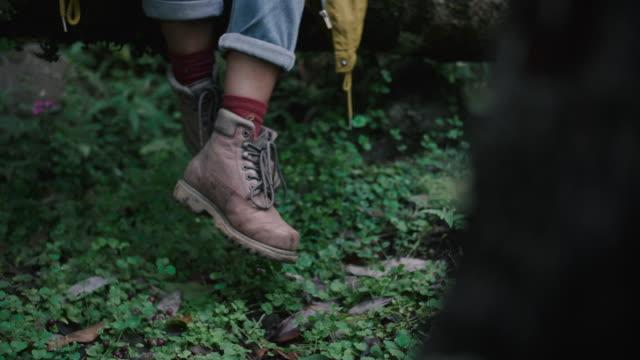 vídeos de stock e filmes b-roll de legs of an young woman explorer swinging in the nature - articulação humana