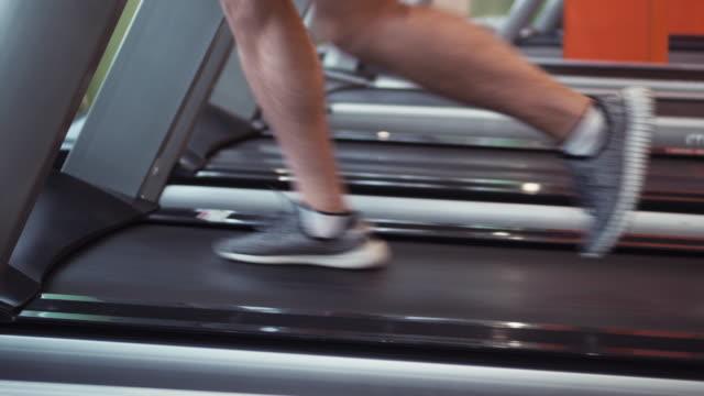 vídeos y material grabado en eventos de stock de piernas de atleta corriendo en caminadora en el gimnasio - máquina de andar y correr