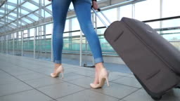 Legs of business woman going through hall of terminal with her luggage. Girl in high heels stepping and roll suitcase on wheels. Concept of work trip or travel. Slow motion Close up