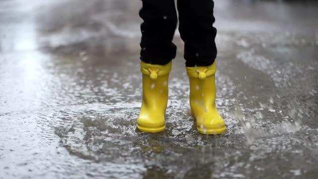 vidéos et rushes de jambes de l'enfant dans des bottes jaunes en caoutchouc sautant dans des flaques d'eau - bottes