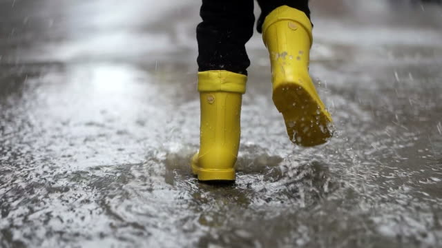 legs of child in yellow rubber boots jumping in puddles - raincoat stock videos & royalty-free footage