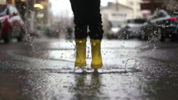 Legs of child in yellow rubber boots jumping in puddles
