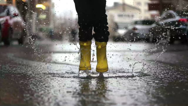 legs of child in yellow rubber boots jumping in puddles - boot stock videos & royalty-free footage