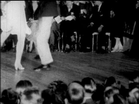 b/w 1925 legs of couple dancing charleston at dance marathon / chicago / newsreel - bロール点の映像素材/bロール