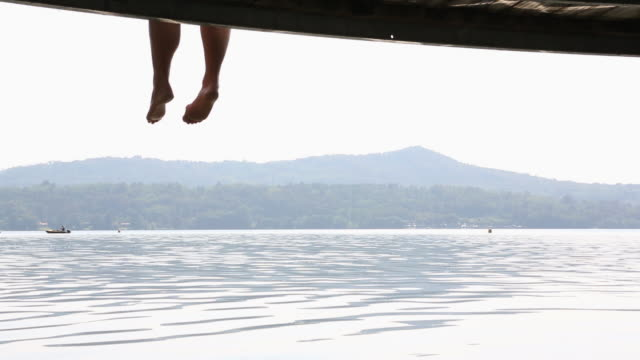 legs of couple dangle from wooden pier above lake - human limb stock videos & royalty-free footage