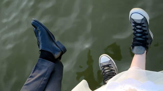 vídeos y material grabado en eventos de stock de piernas de pareja sentada en el banquillo de agua - novia relación humana