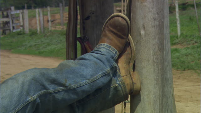 MS Legs of cowboy wearing dirty jeans and boots as he rests his feet up against a pole/ Brazil