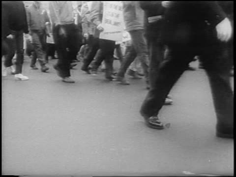 B/W 1967 legs of crowd of antiwar demonstrators marching on NYC street with signs / newsreel